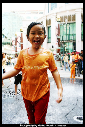 Little girl playing at fountain in Bugis Junction, Singapore