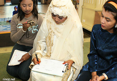 Rinaz signing the marriage document
